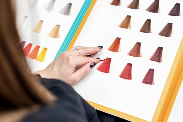 image of a woman choosing red hair samples from palette
